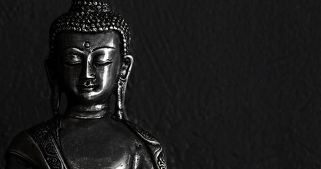 Traditional bronze Buddha statue isolated on black background.