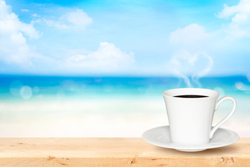 White cup of coffee on wooden table with defocused blue sea, white sand beach background.