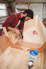 Man preparing a wooden boat frame