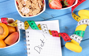 Healthy food, dumbbells, centimeter and notebook for notes, slimming, healthy and sporty lifestyle
