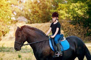 A little boy jockey on horseback . Horseback riding lessons .