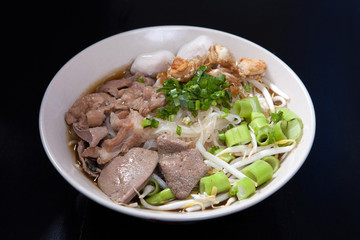 Rice noodle soup with Stewed pork with thai style on black wood