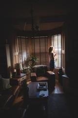 Woman looking through window in living room