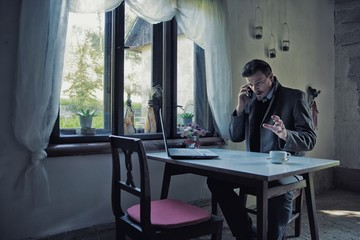 Businessman is Working with Mobile Phone and Laptop