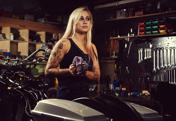 Blond woman mechanic in a motorcycle workshop