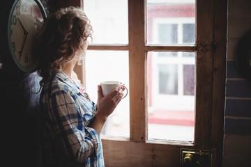 Woman looking through window while having coffee
