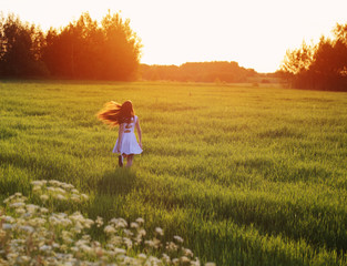 appy young girl running in the field at sunset