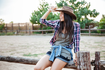 Cheerful relaxed young woman cowgirl sitting on fence and smiling