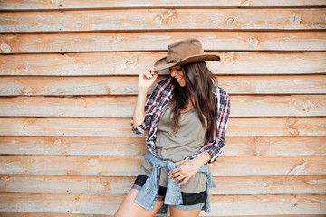 Cheerful cute young woman cowgirl standing and laughing
