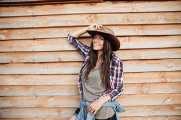 Happy attractive young woman cowgirl standing and smiling