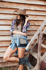 Cheerful attractive young woman cowgirl standing and smiling