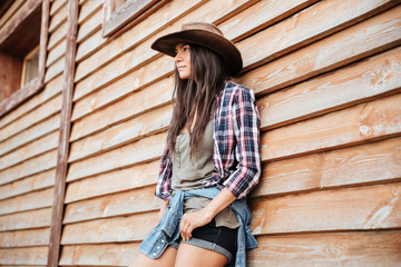 Attractive young womna cowgirl in hat standing near the house