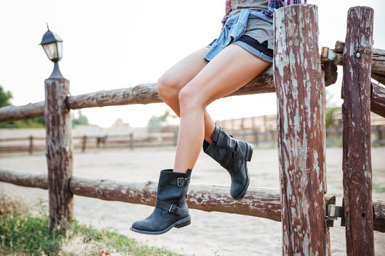 Legs of young woman cowgirl in shorts sitting on fence