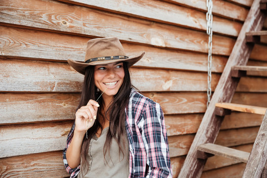 Smiling woman cowgirl in hat standing near the house