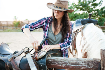 Woman cowgirl in hat preparing saddle for riding horse