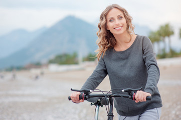Leisure day at the beach. Attractive young blond woman with beautiful curl long hair walking with a bicycle against mountains background.