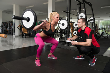 Gym Coach Helping Woman On Legs