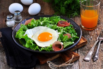 Fried egg with lettuce, arugula, parmesan and jamon. Rustic food.