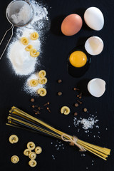 Traditional and black uncooked Italian pasta Linguine, Italian pasta Cappelletti with white and brown chicken eggs, broken white egg, flour, metal sieve and spices on black stone background.