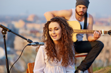 Young beautiful girl singing with a guitar player outdoor