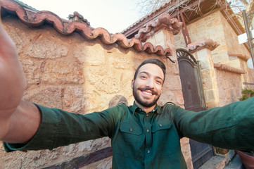 I love travel! Handsome young man in shirt holding camera and making selfie and smiling while standing against old town background