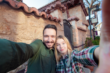 Capturing a happy moment. Beautiful young multi ethnic couple bonding to each other and smiling while making selfie with old town sightseeing in the background.