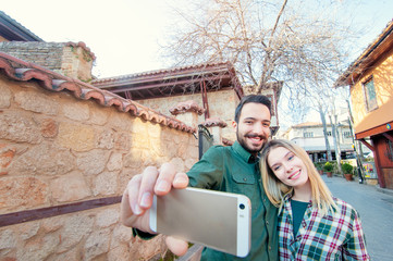 Catching the bright life moments. Beautiful young loving couple making selfie with smart phone and smiling while traveling by Europe.