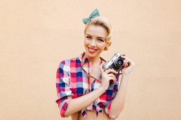 Happy smiling pinup girl in yellow dress using vintage camera