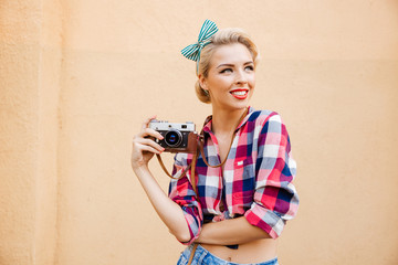 Beautiful cheerful pinup girl in yellow dress using vintage camera