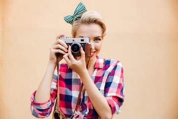 Smiling attractive young woman taking photos using old camera
