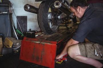 Mechanic using hydraulic lift