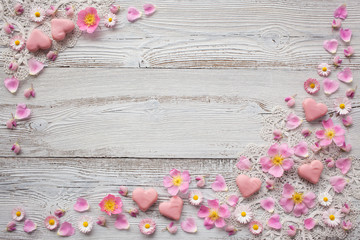 Light wood background with pink flowers, petals,  candy in the shape of heart and lace