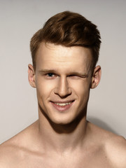 Fashion closeup portrait of young handsome red hair happy smiling man winking