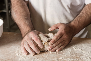 Detail on hand baker kneading dough on a black board with flour powder. The concept of baking and pastry shops.