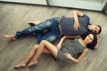Young sexy casual dressed couple relaxing on wooden floor. Beautiful brunette girl with long brunette woman and handsome man