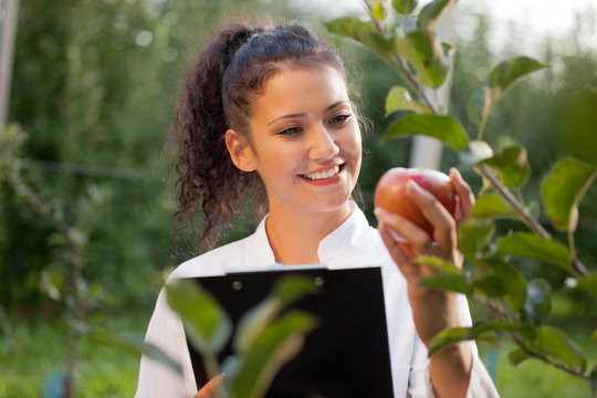 happy young woman agronomist with green apple in her hand