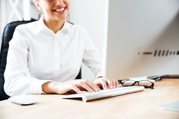 Cropped image of a smiling happy businesswoman typing on keyboard