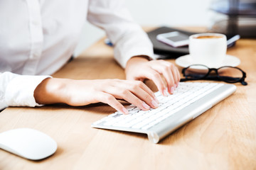 Cropped image of women's hands typing on keyboard