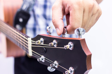 Person tuning a guitar over white background