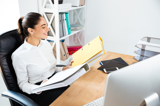 Businesswoman holding yellow binders at office
