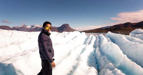 Man traveler enjoying stand on  ice , greenland glacier. icecap of south greenland, warm winter present effect