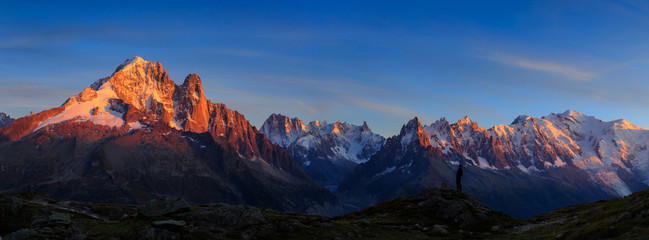 Fotomurales - Man enjoying the view of the Alps, with Aiguille Verte and Les Drus, near Chamonix during sunset.