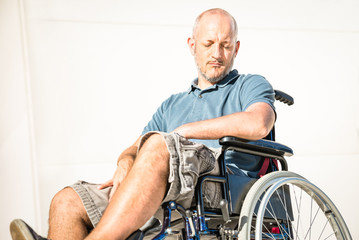 Disabled man with handicap on wheelchair in depression moment - Disability concept with powerless unhelped person sitting alone on wheel chair - Social issues with invalid guy on difficulties
