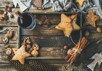 Glass of mulled wine in wooden tray with Christmas decoration toys, gingerbread cookies, nuts, cinnamon, anise, sugar powder and pine cones over rustic wooden background, top view, copy space