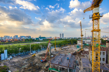 Construction site with cranes on sunset time and bangkok city background