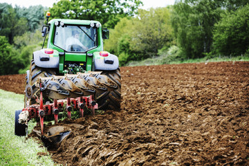 A tractor ploughing the soil in a field, harrowing.