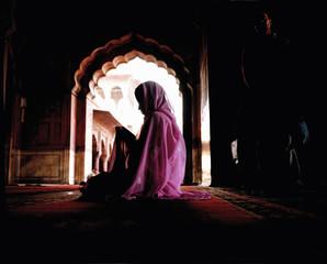 Woman wearing pink veil and sari sitting on floor