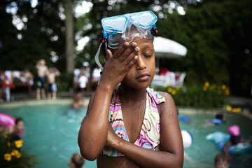 Portrait of a young girl wearing swimming goggles and a bikini, standing by a swimming pool.
