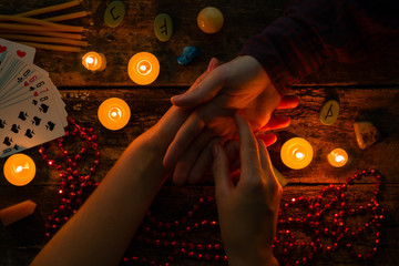 fortuneteller reads fortunes by hand on a background of candles and runes
