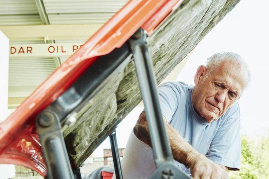 Senior man repairing a car, looking under bonnet.